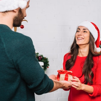 Man presenting gift for happy woman