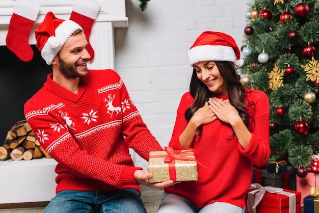 Man presenting gift to woman near christmas tree