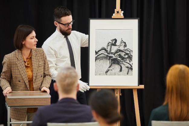 プレゼンテーションで絵画を提示する男