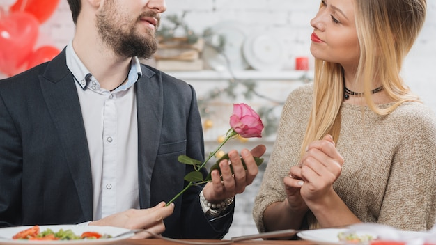 Man presenting pink rose to woman