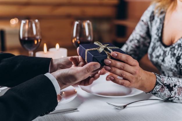 A man presents a gift to a woman at dinner
