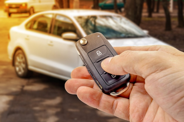 Man presses button on ignition key with immobilizer on the background of the car