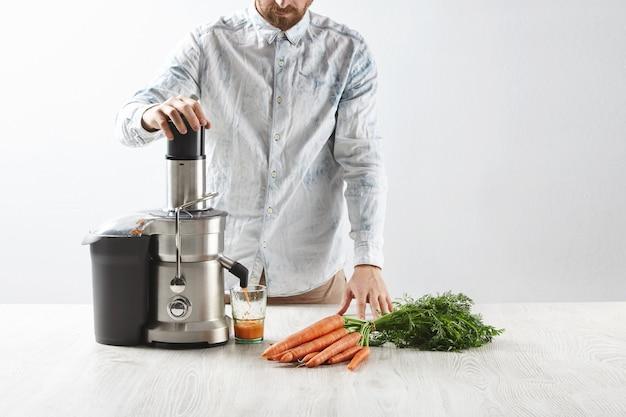 Мужчина выжимает морковь внутри металлической профессиональной соковыжималки, чтобы приготовить вкусный сок на завтрак из свежей моркови, наливаемой в прозрачное стекло.