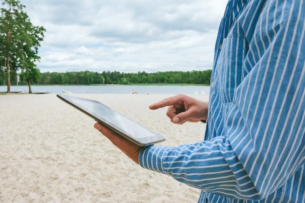 男はタブレットを指で押します。ビーチと自然を背景に。