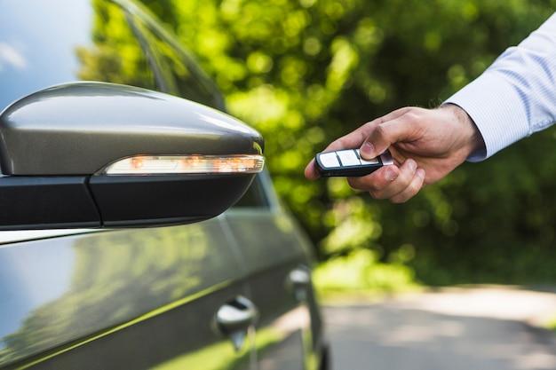 Мужчина нажимает кнопку дистанционного управления, чтобы открыть дверцу автомобиля