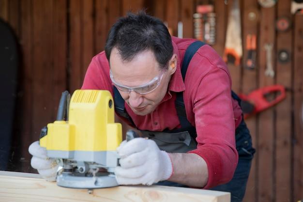 Мужчина обрабатывает древесину с помощью фрейзера в мастерской загородного дома