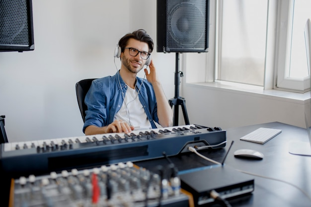 Man produce electronic soundtrack in project at home
