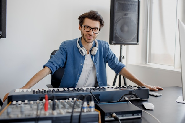 Man produces electronic soundtrack or track in project at home