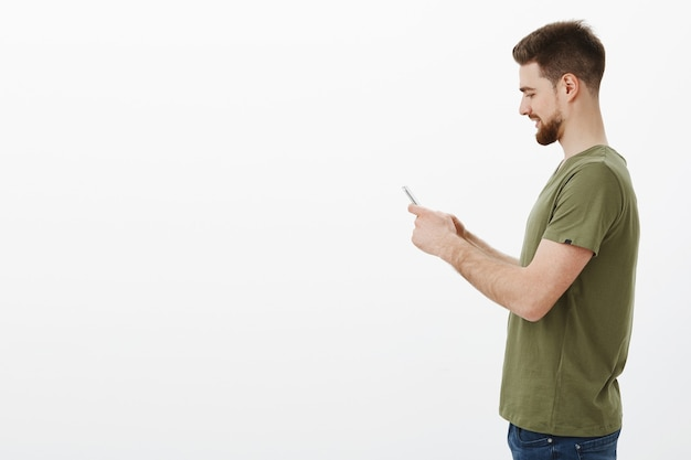 Man in profile with beard holding smartphone and smiling excited as playing interesting online game via mobile phone, using internet to contact friend, sending cool meme over white wall