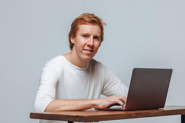 Программист человек, сидящий за ноутбуком на сером светлом фоне