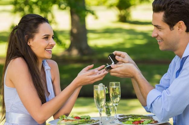 彼らは屋外のカフェでロマンチックな日付を持っている間、男性は女性を提案する