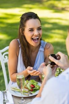 屋外のカフェで陽気な女性を提案する男