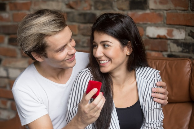 Man proposing to excited woman at home, holding ring box