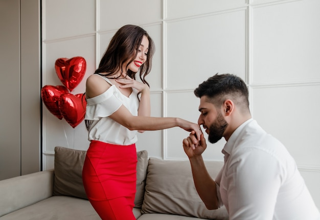 Man proposing to fiancee with a ring and heart shaped balloons at home in apartment