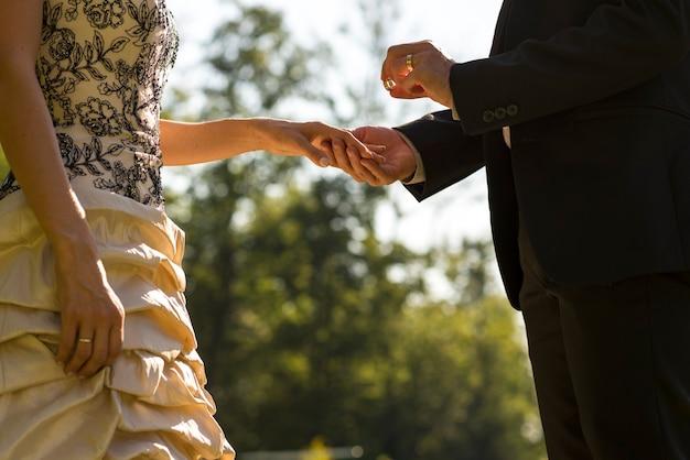 Мужчина делает предложение или женится на своей возлюбленной на открытом воздухе в парке