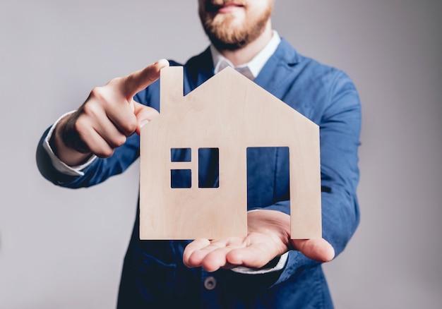 Укомплектуйте личным составом предлагать подписывать полис страхования имущества, агент держит модель деревянного дома. концепция страхования имущества.