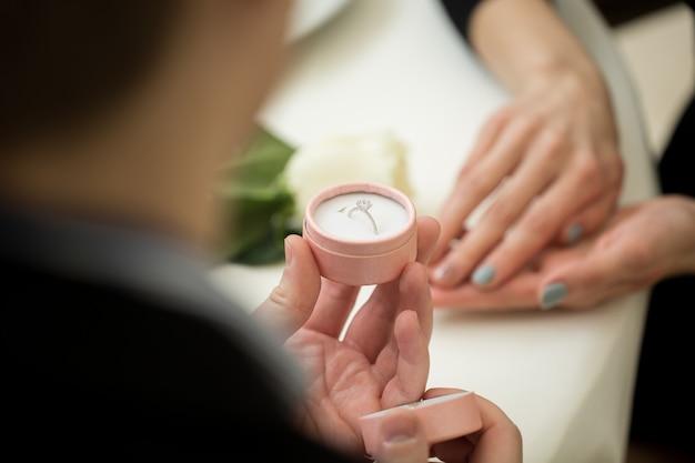 Мужчина делает предложение с бриллиантовым кольцом в ресторане