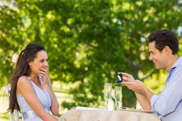 屋外のカフェで女性を提案する男
