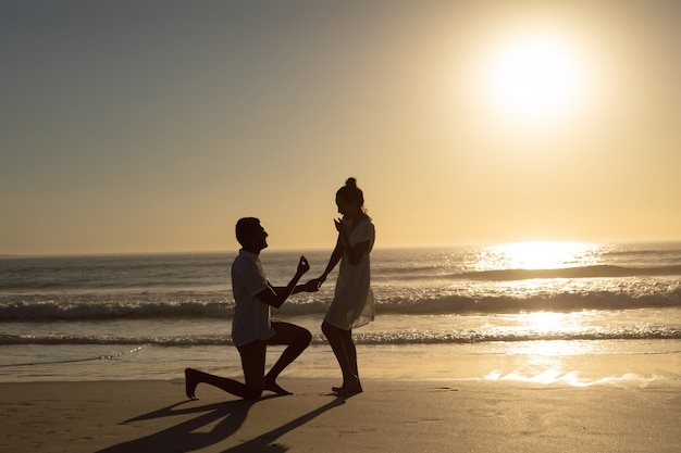 Man proposing woman at seashore on the beach