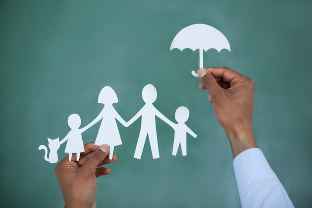 Man protecting paper cut out family with umbrella