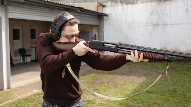 A man in protective glasses and headphones holding a pump action shotgun