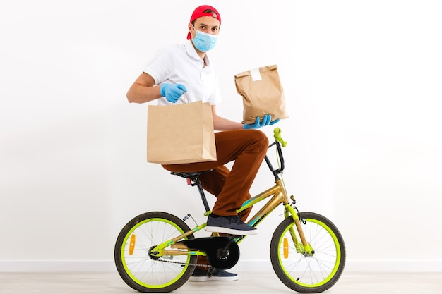 A man in protective mask is delivering food on a bicycle. online shopping and express delivery . quarantine