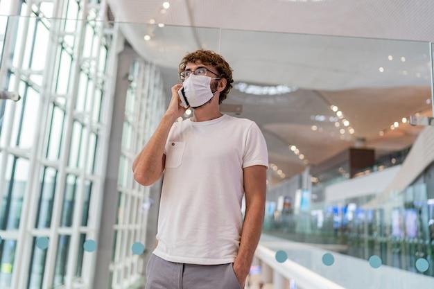 Uomo in maschera protettiva in piedi nella hall dell'aeroporto con lo smartphone