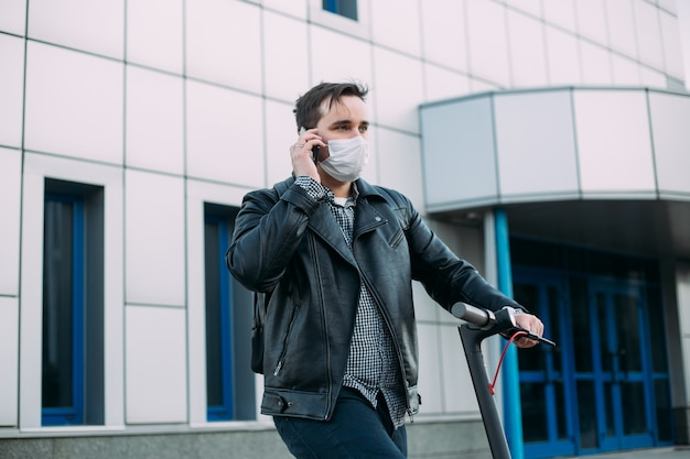 Man in protective mask using mobile phone