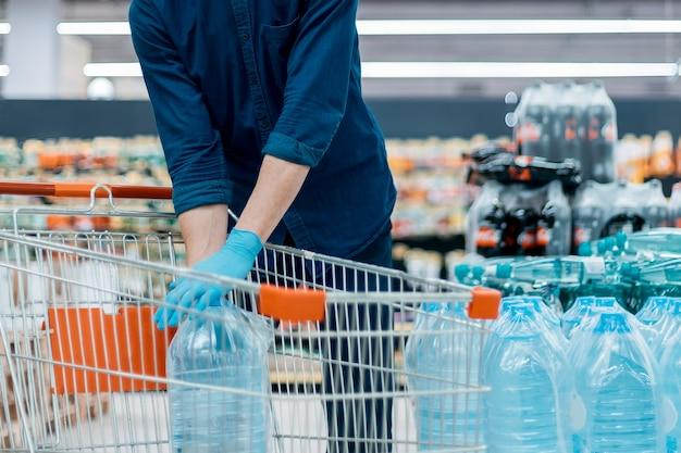 Man in a protective mask with a shopping cart standing in the trading floor. photo with a copy-space