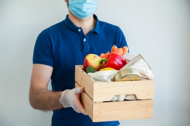 Man in protective medical mask and gloves holding a box full of food