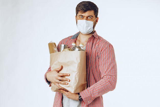 Man in a protective medical mask with a bag from a grocery store