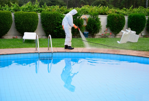 Man in protective overalls disinfects the pool floor