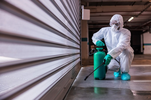 Man in protective sterile uniform crouching and disinfecting garage with disinfectant