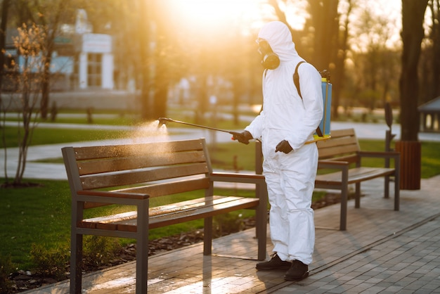 Man in protective suit disinfecting bench in the public park in quarantine city. infection prevention and control of epidemic. covid -19.