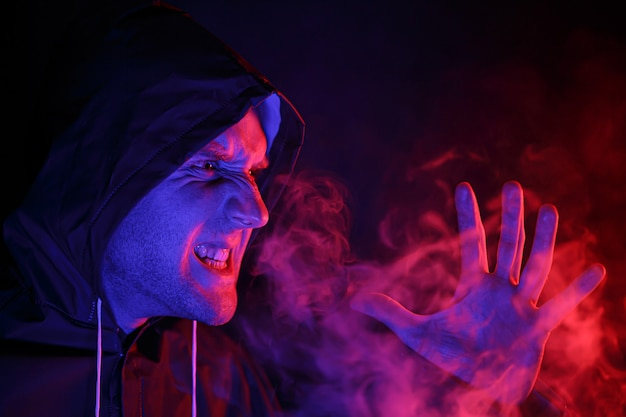 A man in a protective suit exhales smoke. halloween image concept. virus protection. illuminated with colored lights