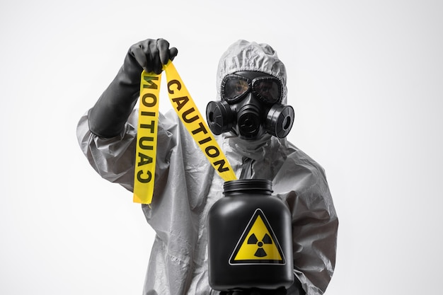 Man in a protective suit and gas mask holding a yellow tape
