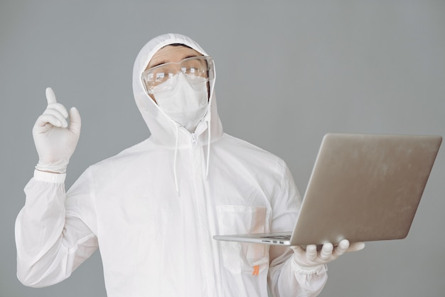 Man in protective suit and glasses on grey wall