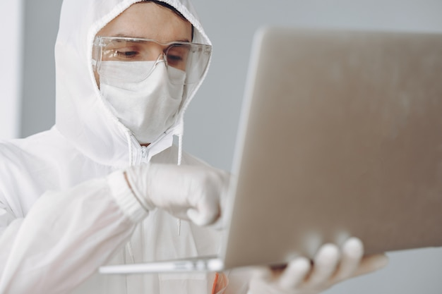 Man in protective suit and glasses working at laboratory