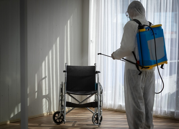 Man in protective suit and mask disinfecting the empty wheelchair in the hospital room from coronavirus