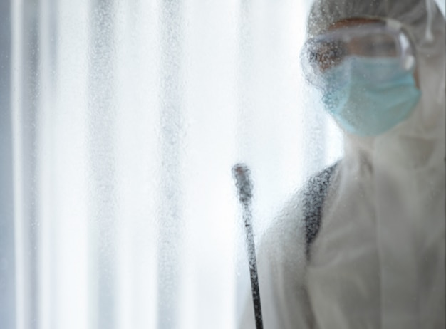 Man in protective suit and mask disinfection on glass in the hospital room from corona virus / covid-19.
