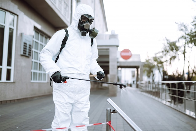 Man in protective suit and mask sprays disinfector onto the railing in the empty public place at dawn in the city of quarantine. covid -19. cleaning concept.