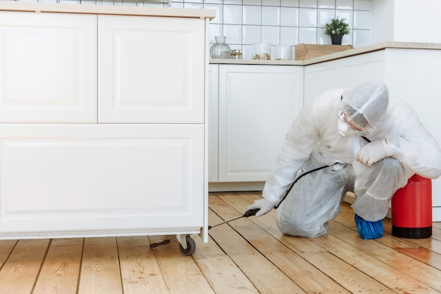A man in a protective suit with a disinfectant spray to disinfect household items and furniture