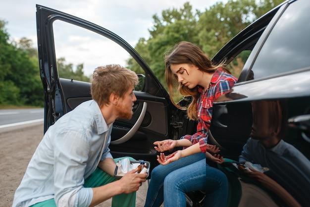 Мужчина оказывает первую помощь женщине-водителю после автомобильной аварии на дороге. автомобильная авария. разбитый автомобиль или поврежденный автомобиль, автокатастрофа на шоссе