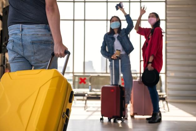 공항 출발 터미널에서 인사하기 위해 손을 흔들며 얼굴 마스크로 친구가 수하물을 당기는 동안 남자