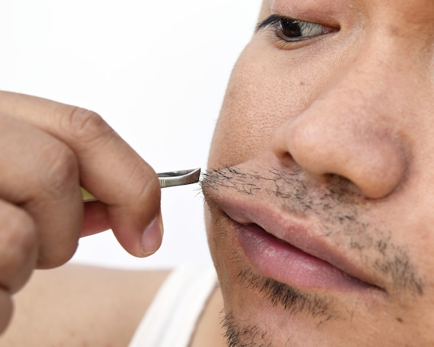 Man pull mustache by tweezers on white background