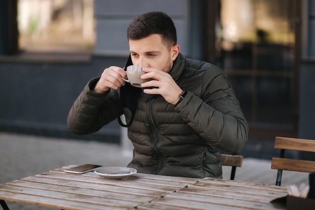 남자는 테라스에서 카푸치노를 마시기 위해 얼굴 마스크를 벗었습니다. 검역 기간 동안 야외 카페에서 남자. 코로나 19.