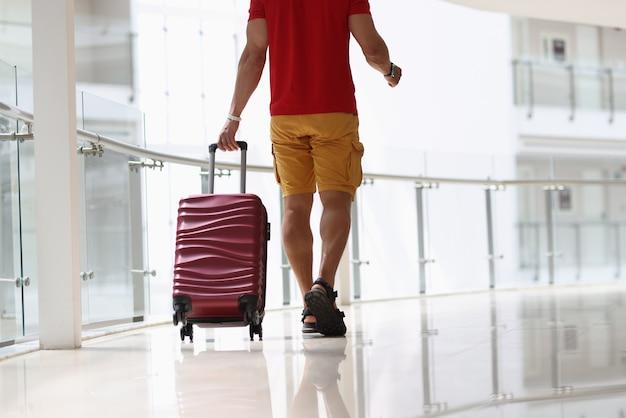 空港のクローズアップで床にバーガンディのスーツケースを引っ張る男