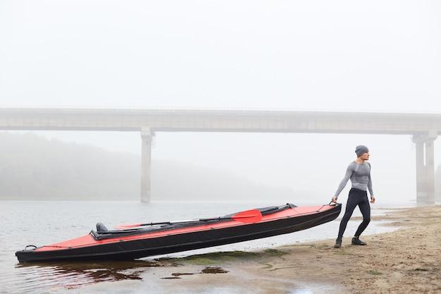 Мужчина тянет каноэ с реки или озера, стоит на берегу реки, смотрит вдаль, позирует в туманный день