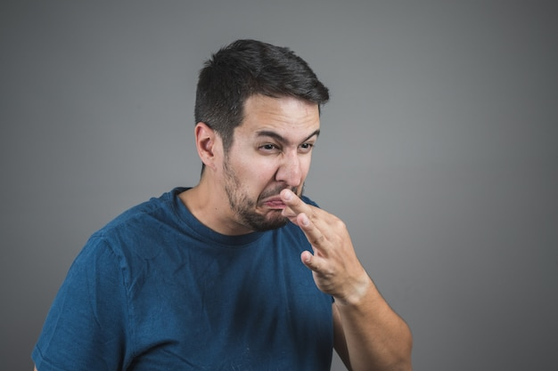 Man pulling something out of his tongue with a face of disgust