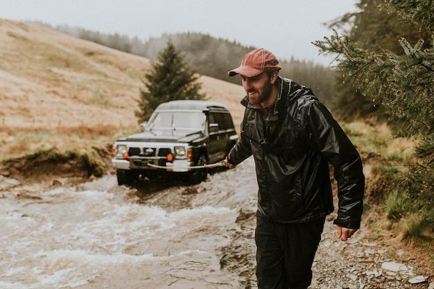 Человек тянет автомобиль буксировочный трос